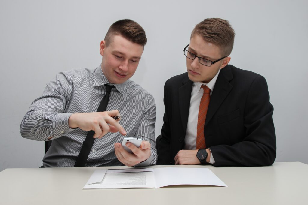 two man watching smartphone